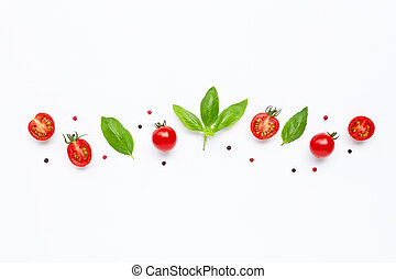 Fresh cherry tomatoes with basil leaves and different type of peppercorns on white background. Top view