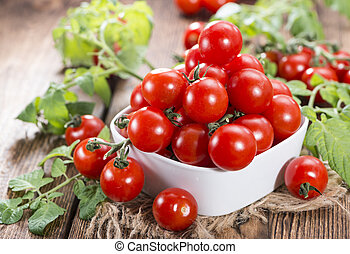 Fresh Cherry Tomatoes with leaves on wooden background