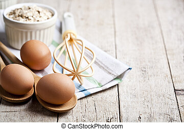 Fresh chicken eggs, oat flakes in ceramic bowl and kitchen utensil on rustic wooden table background.