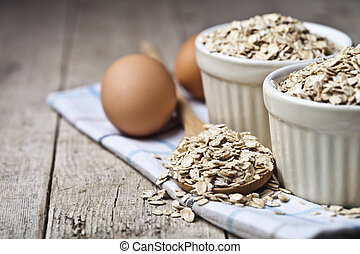 Fresh chicken eggs, oat flakes in ceramic bowl and wooden spoon on rustic wooden table background.