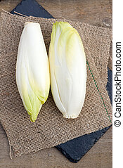 Fresh chicory witloof heads in rustic setting with wooden...