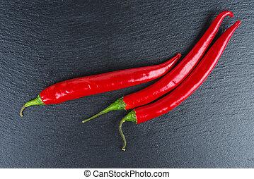 Fresh chili peppers on black stone slate background