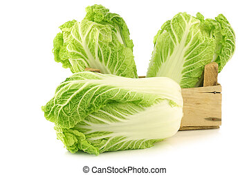 fresh chinese cabbage in a wooden crate on a white...