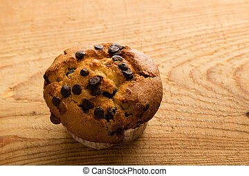 fresh chocolate chip muffin on wooden table