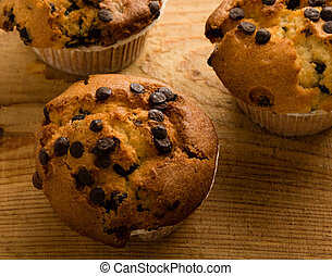 fresh chocolate chip muffins on wooden table