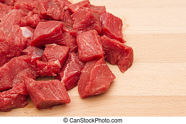 Fresh chopped beef steak on wooden chopping board
