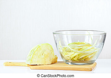Fresh chopped cabbage in a glass bowl on a cutting board