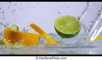 Fresh Citrus fruits fall into the water