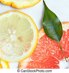 Fresh citrus fruits slices background viewed from above.