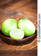 Fresh citrus lime wholes and slice on wood table