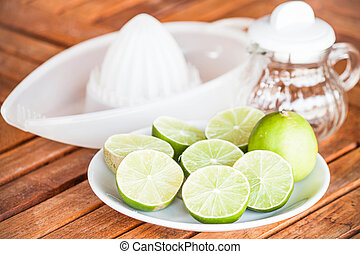 Fresh citrus lime with glass jar and hand squash tool