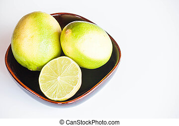 Fresh citrus limes whole and slice in bowl on white background