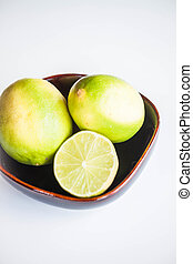 Fresh citrus limes whole and slice in ceramic bowl