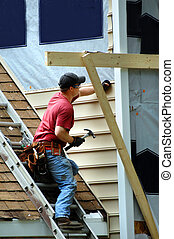 Young carpenter installs new sideing on a two story home. He is holding a hammer and nail.