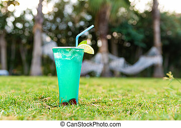 Fresh cocktail with strow on the grass