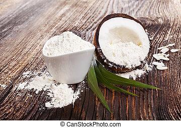 Fresh coconut flour raw coconut half on wooden table. ...