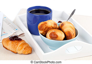 Fresh coffee and tasty croissant in a tray for breakfast.