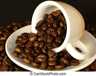 Fresh coffee beans floating out of a white espresso cup