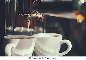 Fresh coffee prepared in the coffee machine. Espresso in white cups. Close-up of drops of coffee.
