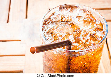 Fresh cola drink with ice on wood table