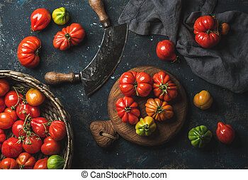 Fresh colorful ripe heirloom tomatoes in basket and wooden board