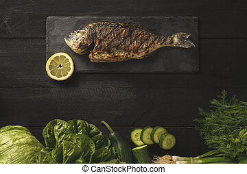 Fresh cooked dorado or sea bream fish with lemon slice on a dark stone with vegetables