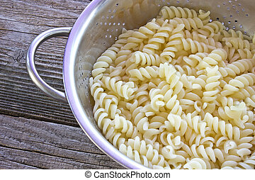 Fresh cooked fusilli pasta in strainer on table