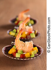 Fresh cooked king prawn with a mix of avocado, mango, red bell pepper, onions on scallop shells served as appetizer (Selective Focus, Focus on the prawn in the front)