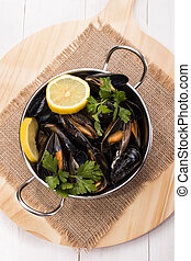 cooked mussels with lemon slices and parsley in a metal bowl