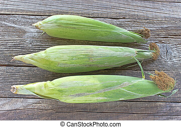 Fresh corn cobs on wooden  background