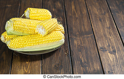 Fresh corn cobs on wooden table in rustic style
