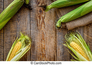 Fresh corn on cobs on rustic wooden table top view copyspace