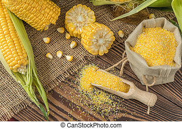 Fresh corn on cobs on rustic wooden table, top view. Dark wooden background freshly harvested organic corn. Corn grits in cloth sack.