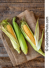 Fresh corn on cobs on rustic wooden table top view