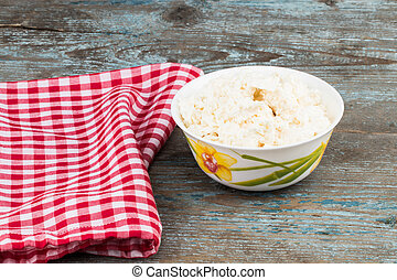 Fresh cottage cheese in a bowl on old wooden background.