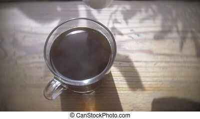 fresh cream poured into a black strong coffee. dark...