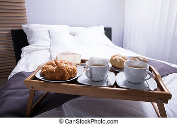 Croissants And Cup Of Tea On Bed