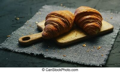 Fresh croissants on chopping board - Two fresh croissants...
