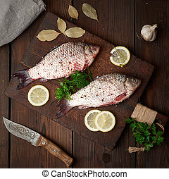 fresh crucian fish sprinkled with spices and lemon slices