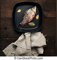 fresh crucian fish sprinkled with spices and lies in a black square pan,