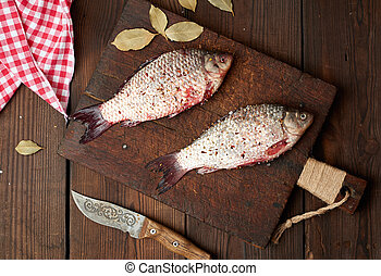 fresh crucian fish sprinkled with spices lies on a brown wooden cutting board