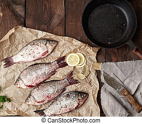 fresh crucian fish sprinkled with spices lies on brown crumpled paper