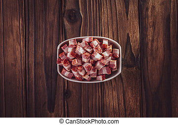 Fresh cubes of bacon isolated on the wood background - Top view