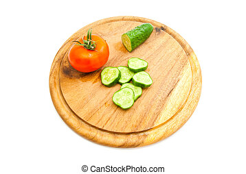 fresh cucumber and red tomato on cutting board