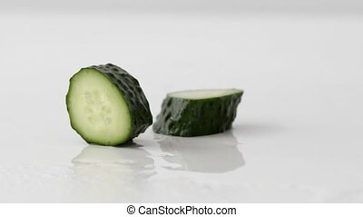 Fresh cucumber is broken into pieces while falling on a wet...