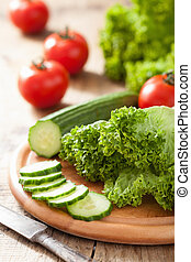 fresh cucumber tomatoes and salad leaves on chopping board