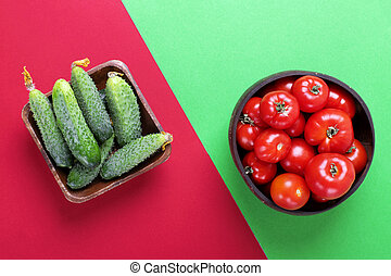 Fresh cucumbers and tomatoes in wooden bowls
