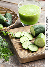 Fresh cucumbers on cutting board on grey wooden background