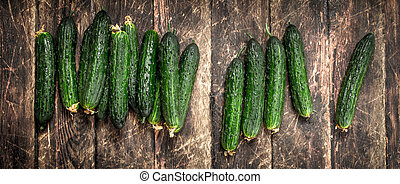 Fresh cucumbers. On wooden background.