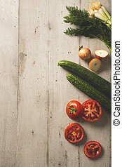 Fresh cucumbers, tomatoes onions and dill on a wooden surface